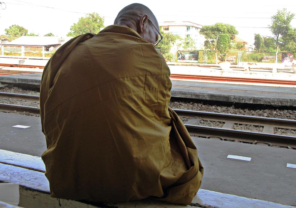 Monje esperando en la estación de tren de Ayutthaya
